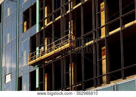 Suspended Construction Craddle Near Wall Of Hightower Building With Ventilated Facade On Constructio