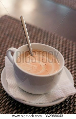 A White Mug With A Spoon And Hot Cappuccino Stands On A Saucer. A Small Cup On A Saucer With A Napki