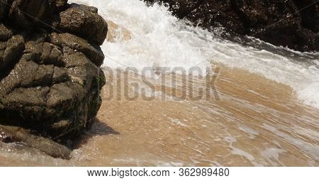 A Closeup Of The Water Crashing Against The Sand And Rocks On Mayto Beach In Jalisco, Mexico.