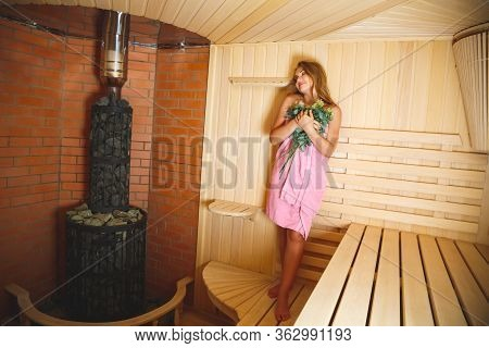 The Lovely Young Girl Costs In A Sauna And Presses To Herself A Bath Broom From Branches. A Light Ba