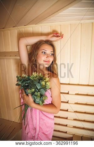 The Lovely Young Girl Costs In A Sauna And Presses To Herself A Bath Broom From Birch Branches