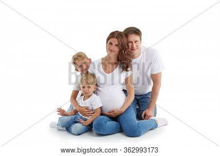 Friendly family. Young pregnant woman with two children and her husband are sitting, isolated on a white background.  Happy parents. Pregnant mother and father with two sons.