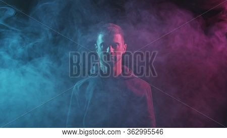 Portrait of computer hacker in hoodie. Obscured dark face in neon light. Data thief, internet fraud, darknet and cyber security.