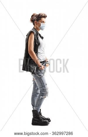 Full length profile shot of a punk woman wearing a protective medical mask isolated on white background