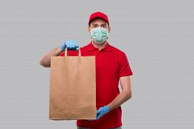 Delivery Man Wearing Medical Mask And Gloves With Paper Bag In Hands. Red Uniform Delivery Boy. Home
