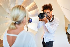 Photographer with camera takes portrait photos of a woman in the photo studio
