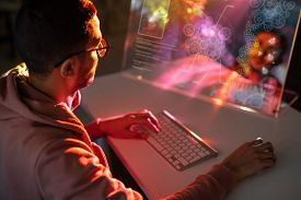 Over shoulder view of young engineer in glasses sitting at table and designing 3D model on computer