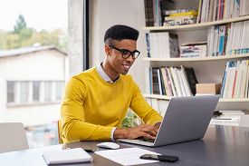 African american businessman using laptop at modern office. Happy creative young man feeling successful after receiving approval mail and working from home. Smiling student studying on computer.