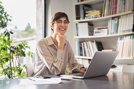 Successful young business woman sitting in creative office and looking at camera. Portrait of happy entrepreneur working on computer. Smiling businesswoman using laptop while working from home.