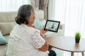 Back View Of Elderly Woman Making Video Call With Her Doctor With Her Feeling Sore Throat On Digital