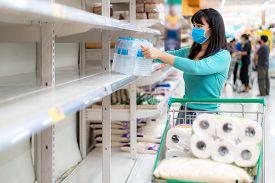 Asian Woman Looking At Supermarket Empty Drink Water Bottle Shelves Amid Covid-19 Coronavirus Fears,
