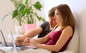 A Man And Woman Work In The Bedroom At A Laptop.. Remote Work At Home During The Coronavirus Quarant