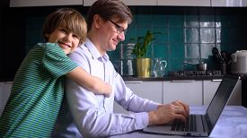 A Man Works In The Kitchen At A Laptop With His Children At Home. Father With Son. Remote Work At Ho