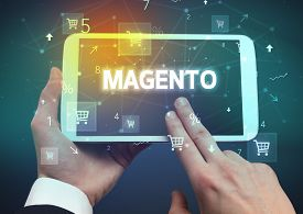 Close-up of a hand holding tablet with MAGENTO inscription, online shopping concept