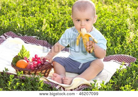 Beautiful little baby boy eats banana
