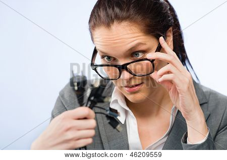 Incompetent businesswoman in geek glasses holding computer cables