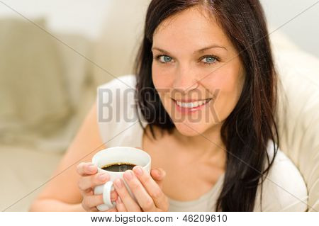 Smiling satisfied woman holding cup of espresso in cozy environment