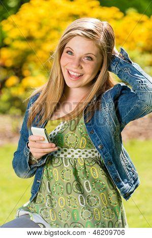 Texting alegre adolescente feminino no parque com smart phone