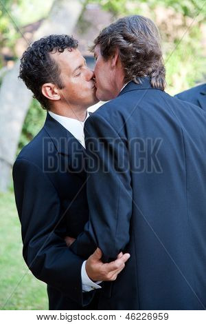 Handsome gay wedding couple, kissing at their wedding ceremony.