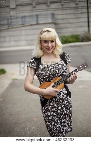 Beautiful Young Woman With Blond Hair Playing Ukulele