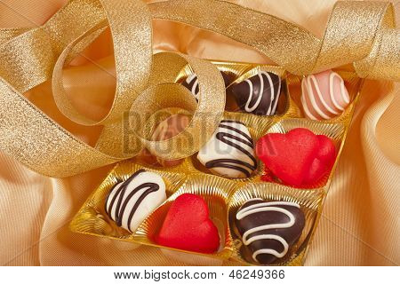 chocolate and marchpane hearts candies on golden silk textured cloth background