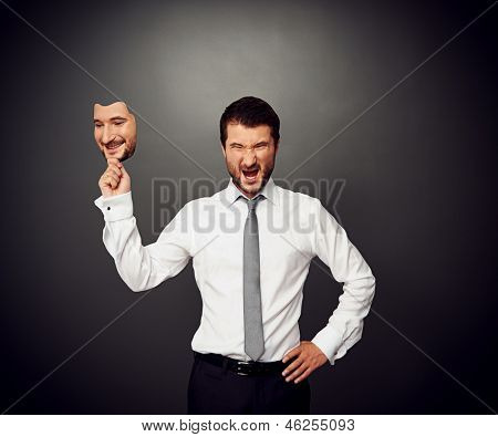 wrathful businessman holding mask with smiley face