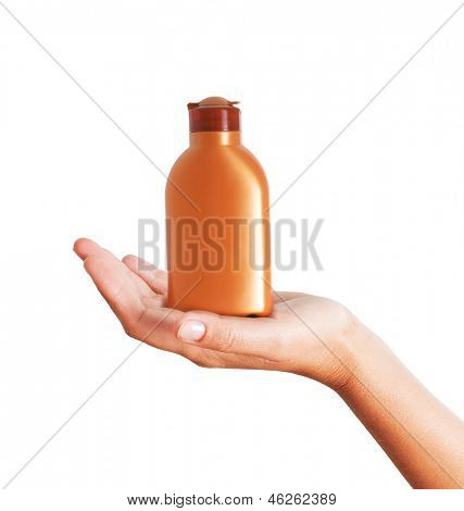 Hand holding plastic bottle for sun lotion isolated on white background.