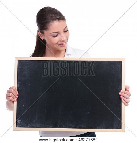 casual young woman holding a blank blackboard and looking at it. isolated on white background