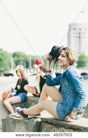 Young happy girl posing in jeans jacket with hat. Outdoors lifestyle poster
