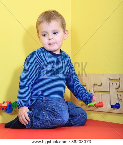 Cute european toddler playing in kindergarten.