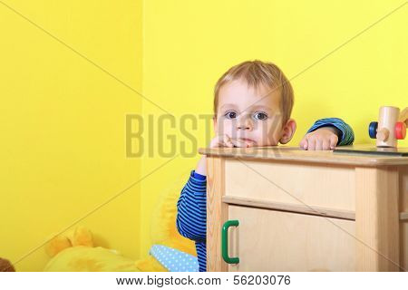 Cute european toddler playing hide and seek in kindergarten. Extra text space on left side.