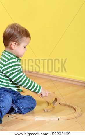 Cute caucasian toddler playing with toy train in kindergarten. Extra text space on upper right corner.