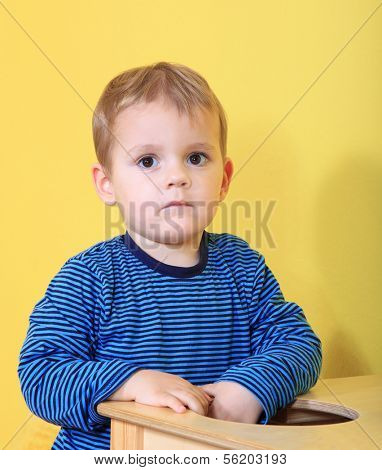 Cute caucasian toddler missing his mum in kindergarten.