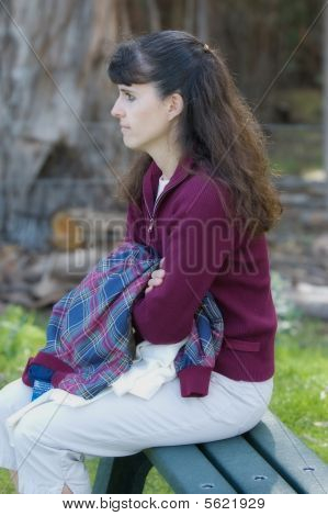 Middle Aged Woman Sitting On A Park Bench Collecting Thoughts