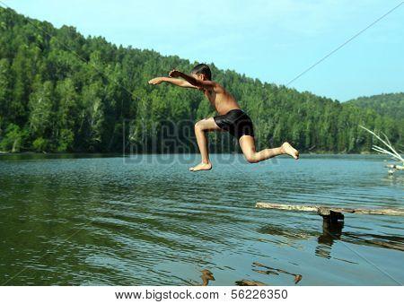 summer vacations - boy jumping in lake