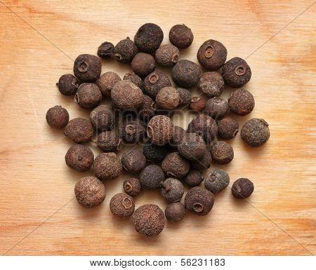 spices - pimento peppercorns macro on wooden board