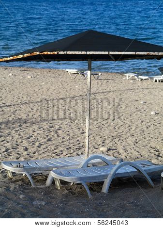 Empty Deckchairs On A Pebble Beach