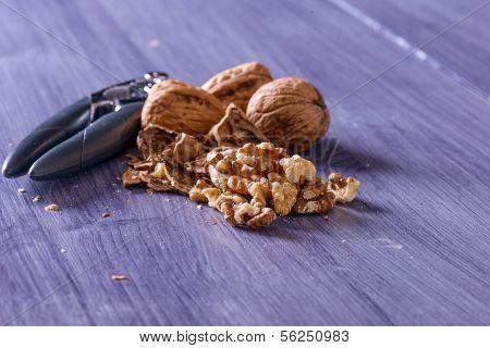 Closeup Of Cracked Walnuts On Purple Table