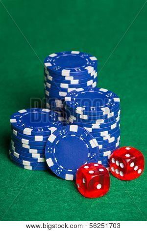 Blue Poker Chips And Two Cubes On The Green Table