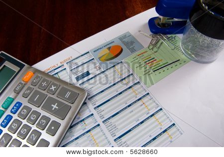 Budget on a wooden desk with a calculator, stapler, and paper clips. poster