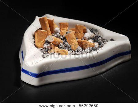 White ceramic ash tray full of cigarette butts on black background