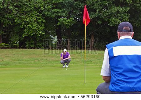 A professional golfer and his caddy reading the green to judge the line of the putt. Series of three photos.
