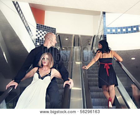 a couple riding down an escalator with the man looking at another woman,cheating concept