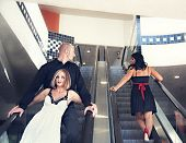 a couple riding down an escalator with the man looking at another woman,cheating concept poster