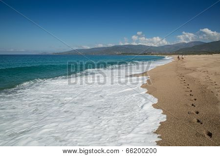 Two People Walking Along The Beach At Sagone In Corsica