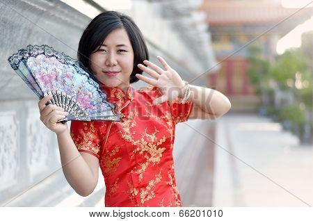 Asian Woman Wearing A Cheongsam With Folding Fan