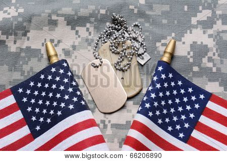 Closeup of two crossed American Flags on camouflage material with dog tags in the middle. The ID tags are blank. Horizontal format filling the frame.