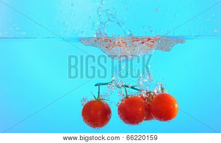 poster of bunch of cherry tomatoes in splash of water Isolated on blue background