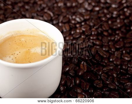 Fresh Cup Of Dark Roasted Coffee With Coffeebeans In The Background