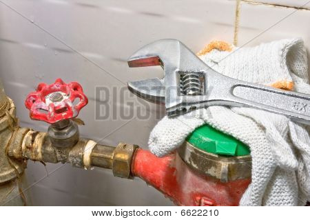 Sanitary equipment still life with old rusty tubes brass valve with red cap red and green water meter white protecti ve cloves and shiny metel wrench. poster